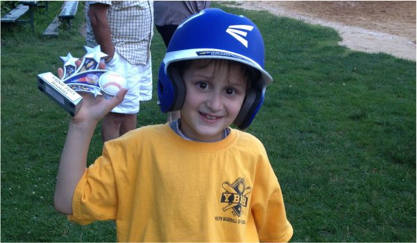 Image of Little Boy with Baseball Helmet and Carrying a Trophy